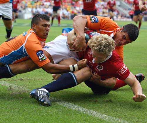 The Reds' Peter Hynes is stopped from scoring a try by the Cheetahs' Hennie Daniller