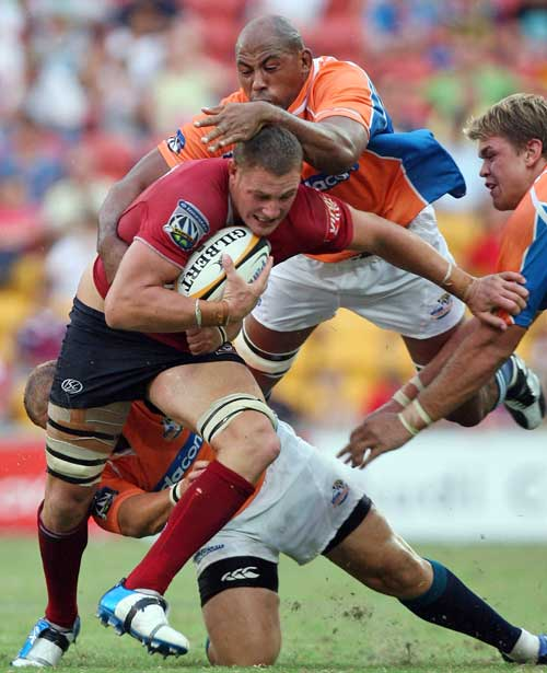 The Reds' Scott Higginbotham is swarmed by the Cheetahs' defence