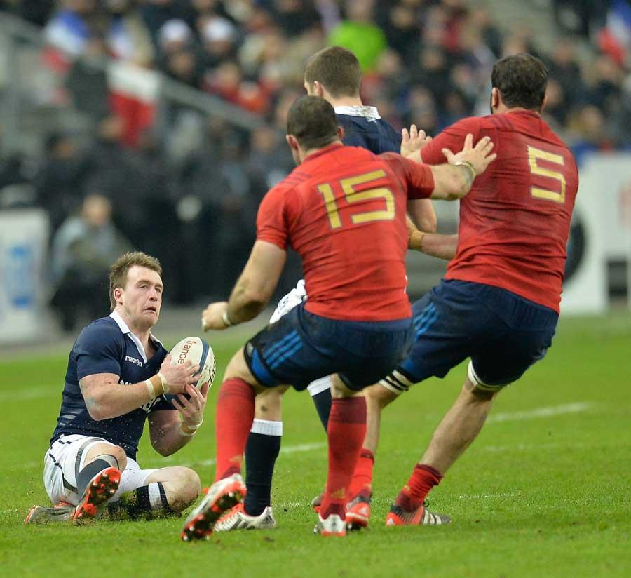 Scotland's Stuart Hogg catches the ball as France close him down