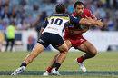 Reds fly-half Karmichael Hunt fends off a tackler
