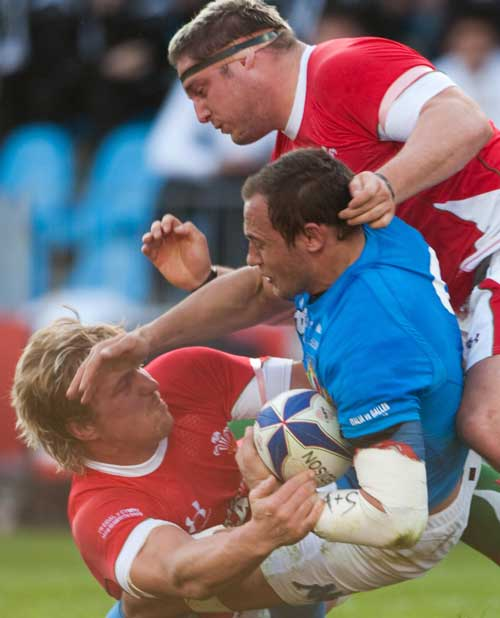 Italy skipper Sergio Parisse is tackled by Andy Powell and Rhys Thomas