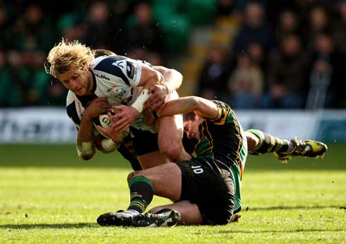Rudi Keil of Sale Sharks is tackled by Roger Wilson and James Downey of Northampton Saints