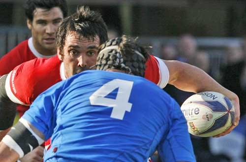 Wales flanker Jonathan Thomas takes on Santiago Dellape