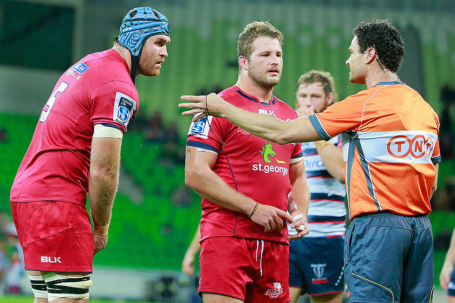 The Reds' James Horwill (L) answers to the referee