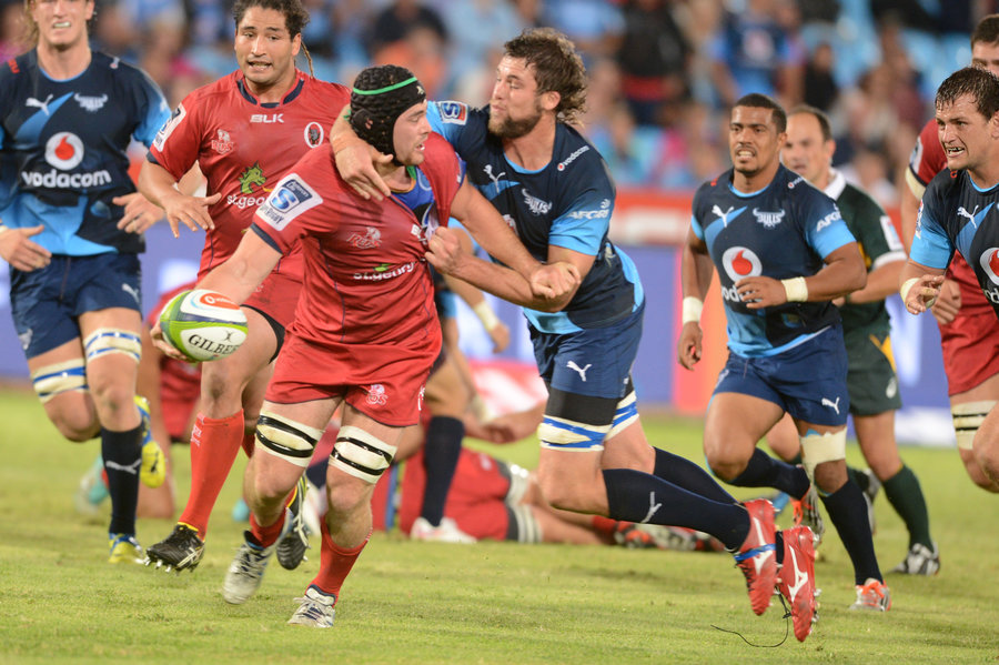 Liam Gill of the Queensland Reds is taken down by the Bulls' defence