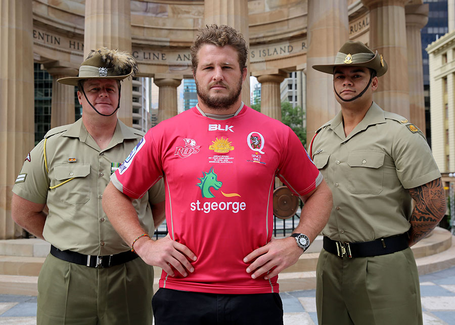 Reds captain James Slipper with Corporal Adam Brown and Private Leone Fifita unveiling the Reds' commemorative ANZAC jersey