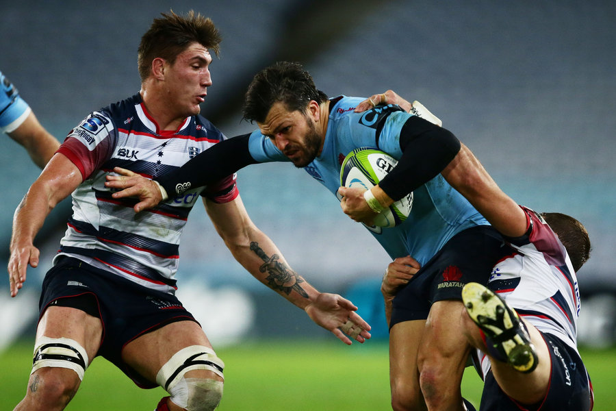 Adam Ashley-Cooper of the Waratahs is taken down by the Rebels defence
