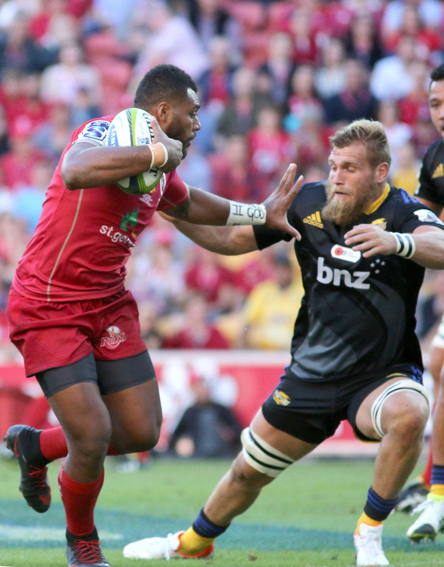 Samu Kerevi of Reds fends off Brad Shields of the Hurricanes before scoring