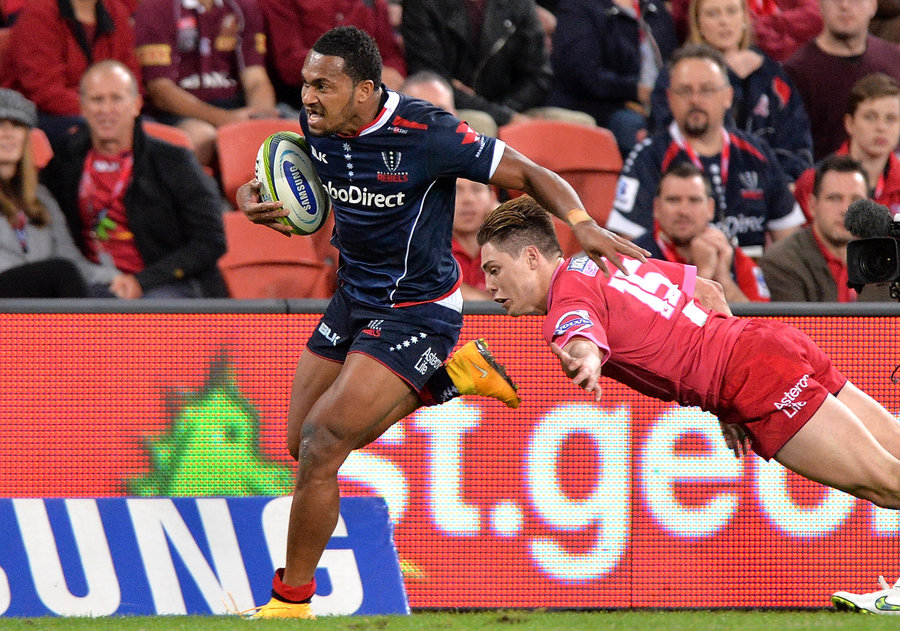 Sefanaia Naivalu of the Rebels breaks away from Reds' James O'Connor