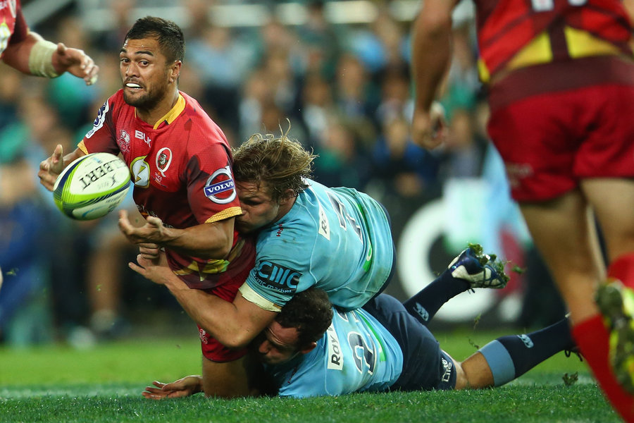 Karmichael Hunt of the Reds is taken down by the Waratahs defence