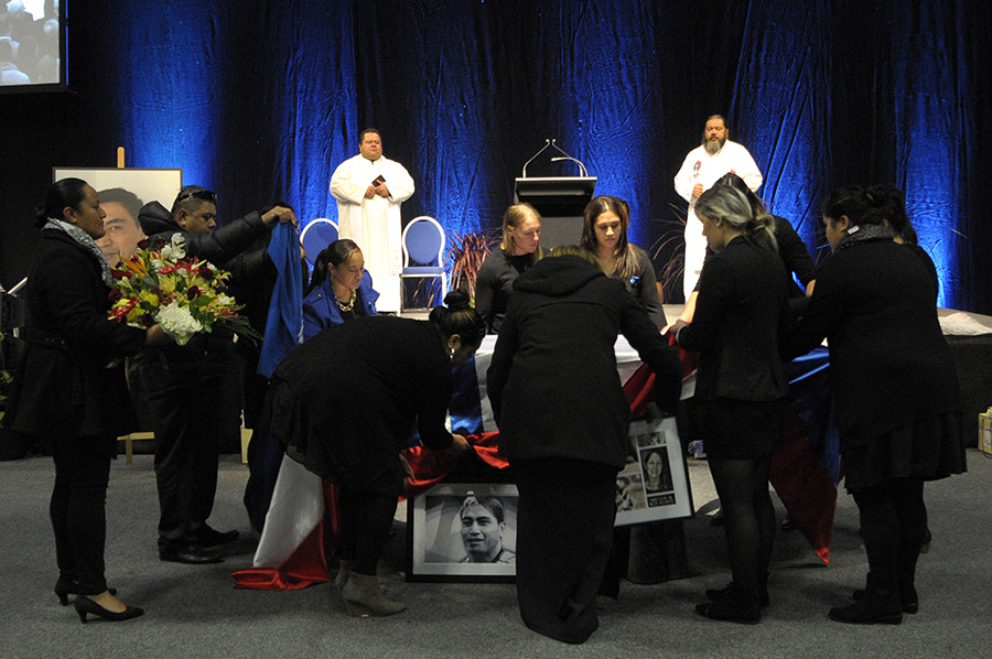 Family members lay a flag over the coffin of Jerry Collins