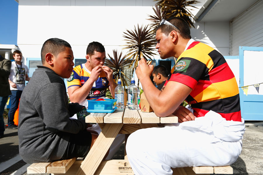 Waikato's Whetu Douglas has lunch with schoolchildren at the table he built during the 2015 ITM Cup season launch