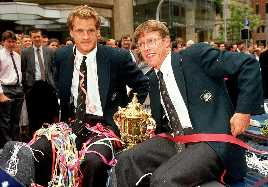 Michael Lynagh (L) and Nick Farr-Jones (R) of the Wallabies pose with the Rugby World Cup durings ticker-tape parade