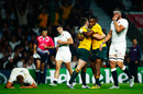 Chris Robshaw and Tom Wood (R) of England react as Bernard Foley of Australia celebrates