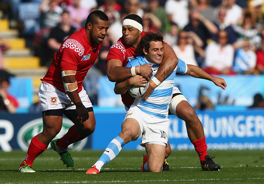 Nicolas Sanchez (R) of Argentina is tackled high by Tukulua Lokotui (C)