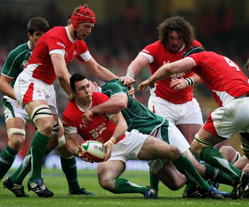 Stephen Jones of Wales looks to offload as he is brought down by Ireland's John Hayes