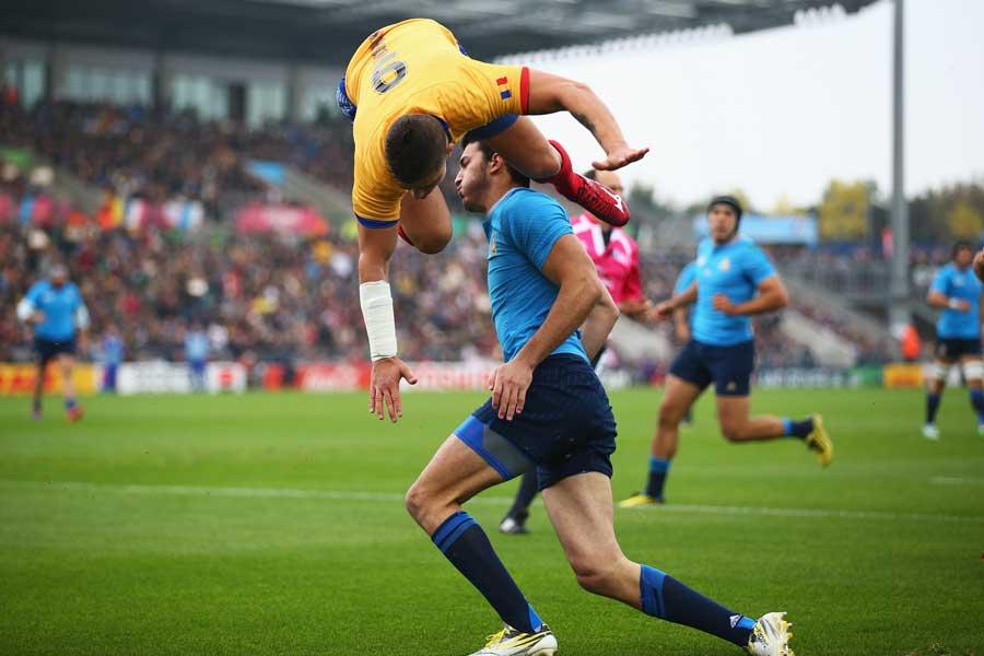 Romania's Valentin Calafeteanu leaps over Leonardo Sarto after the Italian had scored a try