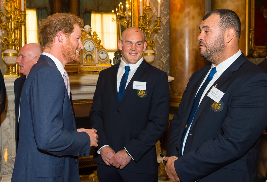 Prince Harry (left) speaks to Australian Rugby Union player Stephen Moore and Australia head coach Michael Cheika (right) at a Rugby World Cup reception at Buckingham Palace