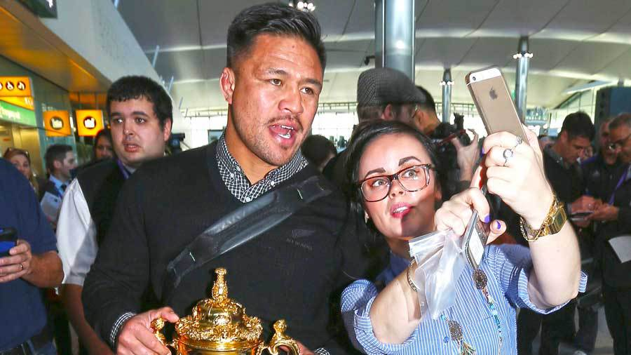New Zealand's Keven Mealamu poses with an All Blacks supporter, Heathrow Airport, London, November 2, 2015