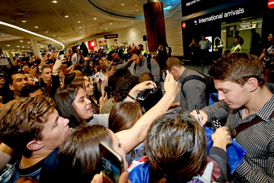 New Zealand's Beauden Barrett and the All Black signs autographs after arriving home