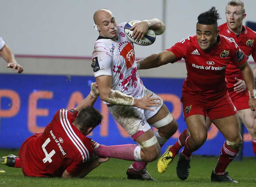 Stade Francais' Sergio Parisse is tackled by the Munster defence