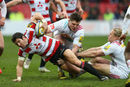 James Hook of Gloucester gets away from a tackle by Harry Sloan and Matt Hopper of Quins