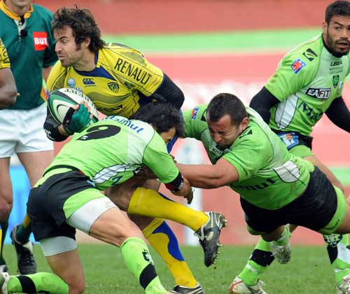 Clermont Auvergne's fly-half James Brock is tackled by the Montauban defence