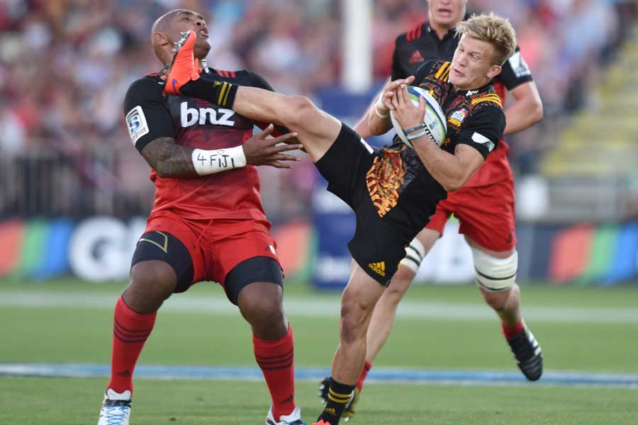 The Chiefs' Damian McKenzie in contact with Nemani Nadolo after collecting a high ball