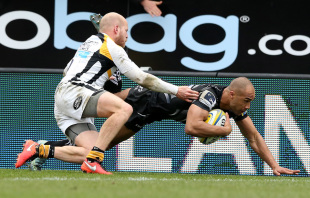 EXETER, ENGLAND - MAY 01: Olly Woodburn of Exeter dives over for the first try despite being tackled by Joe Simpson during the Aviva Premiership match between Exeter Chiefs and Wasps at Sandy Park on May 1, 2016 in Exeter, England.