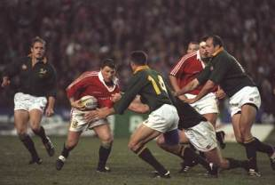 Scott Gibbs charges at the South African defence