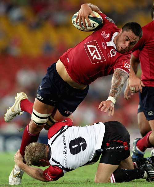 The Reds' Ezra Taylor takes on the Lions defence