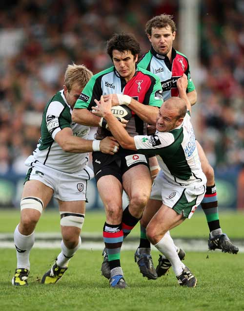 Harlequins' Gonzalo Tiesi is wrapped up by the London Irish defence
