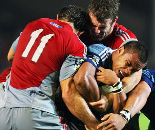 The Blues' Rudi Wulf is wrapped up by the Crusaders' defence