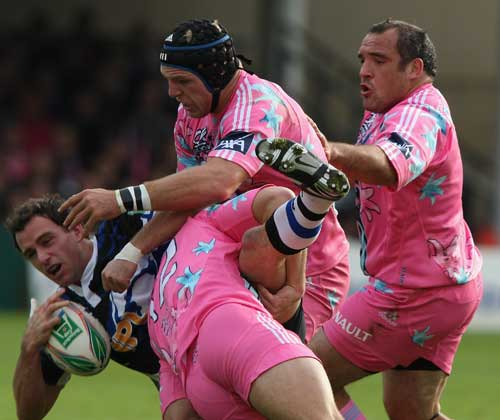 Bath centre Matt Carraro is swamped by the Stade defence