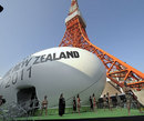 A giant rugby ball pavillion sits below Tokyo Tower while Maoris perform