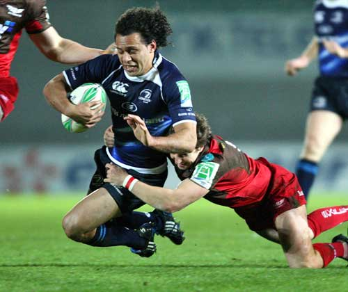 Leinster's Isa Nacewa is tackled by the Scarlets' Martin Roberts