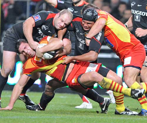 Toulouse's William Servat and flanker Thierry Dusautoir tackle Perpigan's Ovidiu Tonita