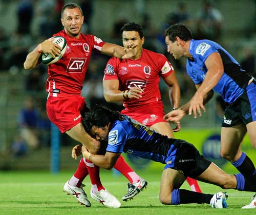 The Reds' Quade Cooper is tackled by the Western Force defence