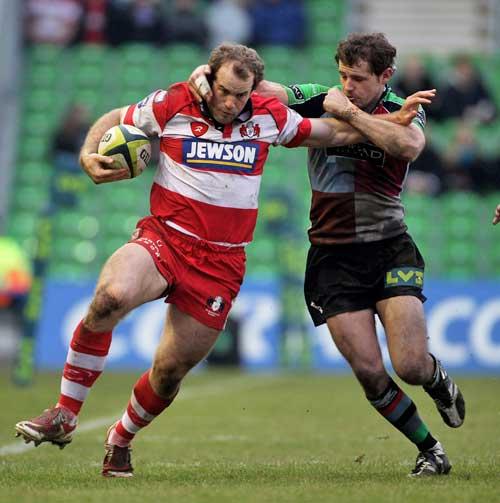 Gloucester's James Simpson-Daniel is tackled by Harlequins' Nick Evans